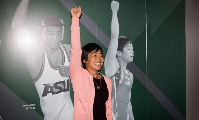 Clarissa Chun poses in front of the Sport For All - Any BODY Can Wrestle exhibit at the National Wrestling Hall of Fame & Museum
